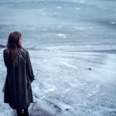 A young woman in glasses and coat stands on a frozen lake.
