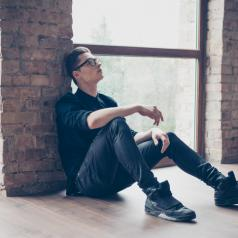 Young adult with short hair and glasses sits on floor against wall, legs out, looking up thoughtfully with serious expression