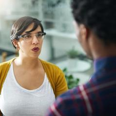 Woman looks at person she is talking to with a mildly annoyed expression on her face.