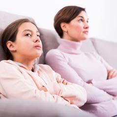 Mother and daughter sit on couch, not acknowledging each other after argument.