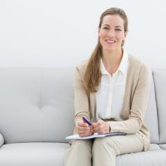 Person with long hair in professional clothing sits on sofa holding paperwork and pen and smiling