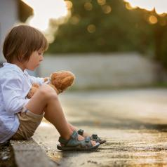 Child sitting on step with stuffed toy at sunset