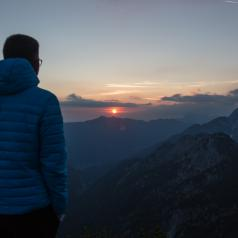 Hiker standing at top of mountain, watching a sunrise