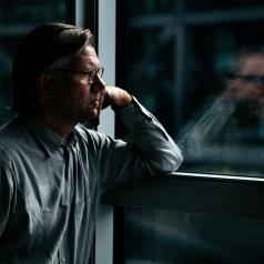 Man stands near window, looking at his reflection