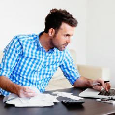 A man works on his finances while kneeling in front of his living room table.