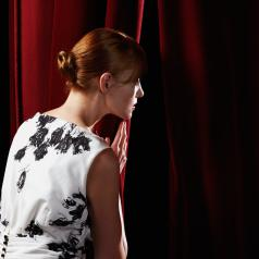 Woman peeking through stage curtain