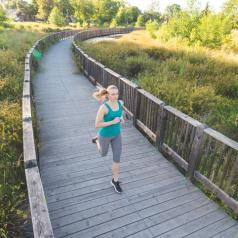Adult with blonde hair in ponytail runs along bridge path in tree-filled park