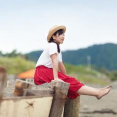 A young woman sits on some logs at the beach.
