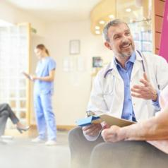 Doctor smiles while talking with patient in office