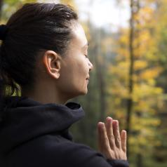 Woman standing in forest with hands together, meditating