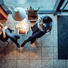 Overhead view of two friends talking in a coffee shop.