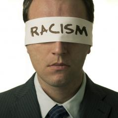 "Blindfolded man with ""racism"" text on the blindfold"