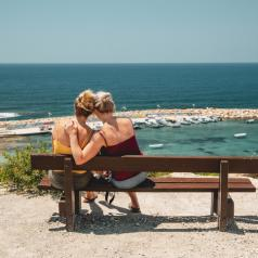 Female couple on bench admiring the sea