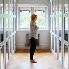 Woman standing in dressing room with mirrors on each of the locker doors