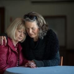 Two senior women hug while sitting at a small library table.