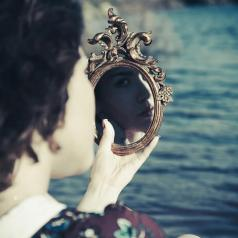 Woman looking into ornate, hand-help mirror