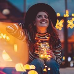 Smiling woman holding glowing string lights