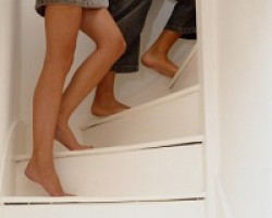 A couple walks upstairs, only their legs and feet showing.