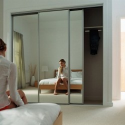 Woman is reflected in mirror while sitting on her bed thinking