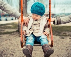 Toddler on a swing is pulled by parents on either side