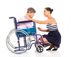 Woman comforting another woman in a wheelchair