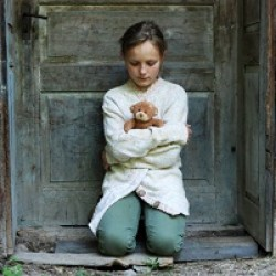Child crouching in door of abandoned house with teddy bear