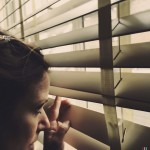 woman peeking out of blinds