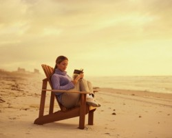 Reading in chair on beach at sunset