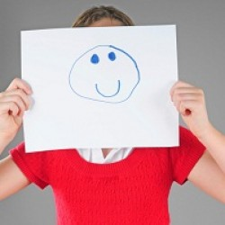 Woman holding drawn smiley face in front of face